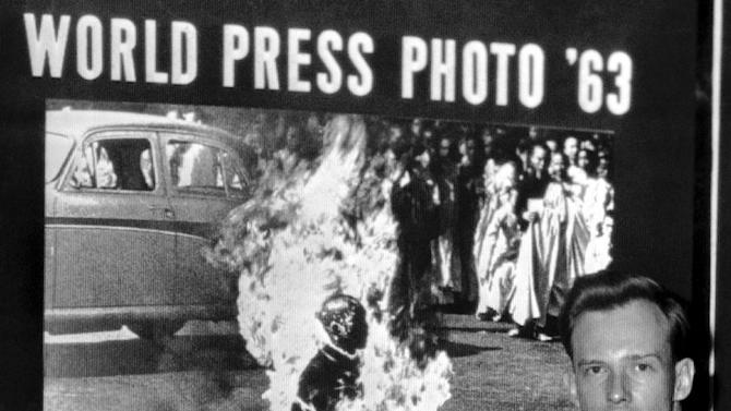 FILE - In this Dec. 14, 1963 file photo, Malcolm Browne, Saigon correspondent for the Associated Press, poses in front of his photo of a Vietnamese Buddhist monk's fiery suicide after the image was selected as the world's best news picture of the year at the Seventh World Press Photo contest in The Hague, Netherlands. Browne, acclaimed for his trenchant reporting of the Vietnam War and the famous photo that shocked the Kennedy White House into a critical policy re-evaluation, has died. He was 81. (AP Photo, File)