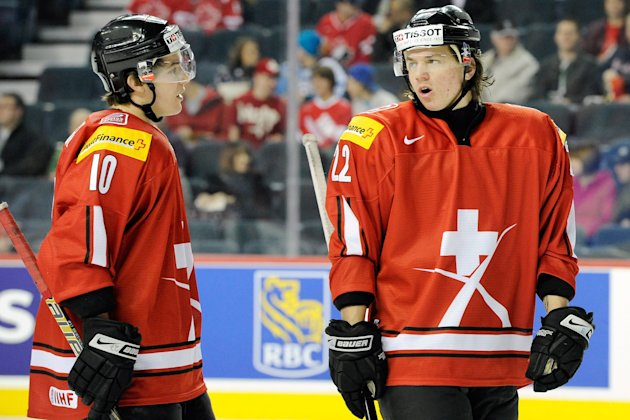 Sven Adrighetto #22 and Alessio Bertaggia #10 of Team Switzerland talk with play stopped during the 2012 World Junior Hockey Championship game against Team Denmark at the Saddledome on January 2, 2012 in Calgary, Alberta, Canada. (Photo by Richard Wolowicz/Getty Images)