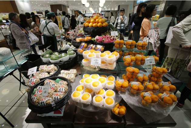 Shoppers buy fruits at a department store in Tokyo
