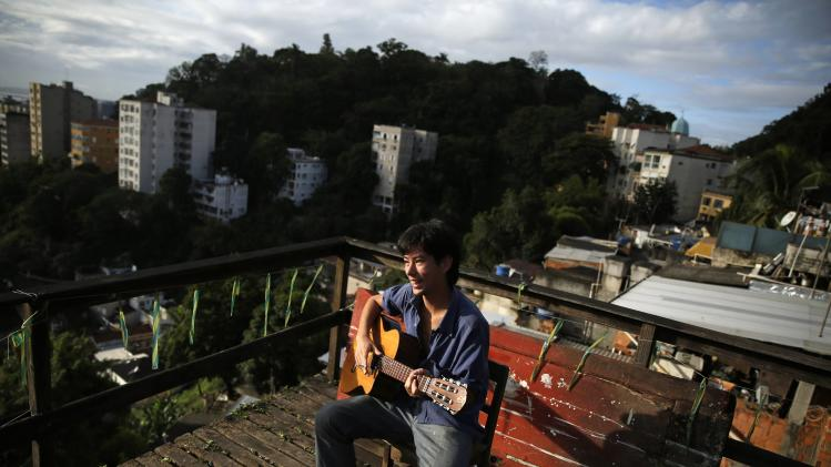 An Argentine fan plays the guitar on a terrace of a rented house in Rio de Janeiro
