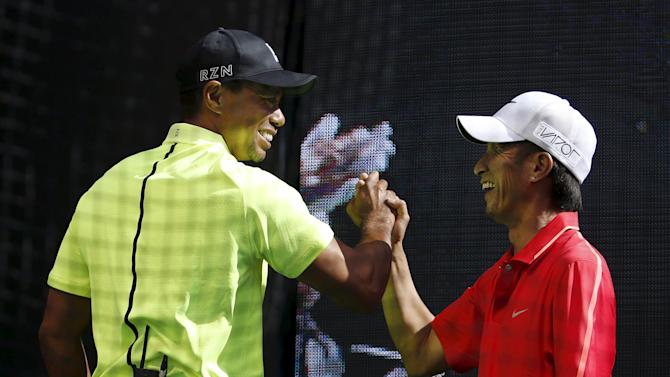 Golfer Tiger Woods of the U.S. high fives with a Japanese amateur golfer during a fan event in Tokyo