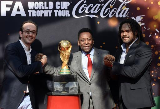 (From L) President of Coca-Cola France, Imad Benmoussa, Brazilian football legend Pele and former French international football player Christian Karembeu pose by the FIFA World Cup trophy, in Paris, o