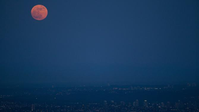 """The """"supermoon"""" appears over Vancouver, British Columbia Saturday May 5, 2012. The moon was the closest it will get to the Earth this year _ and appeared 14 percent larger because of that. At its peak it was about 221,802 miles from Earth. (AP Photo/The Canadian Press, Jonathan Hayward)"""