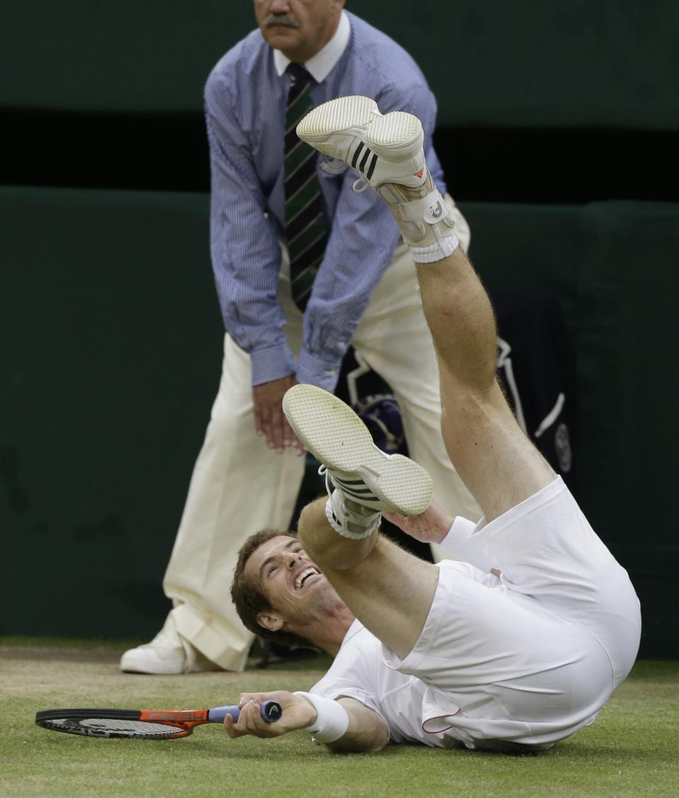 Andy Murray of Britain takes a tumble as he tries to return a shot to Roger Federer of Switzerland during the men's singles final match at the All England Lawn Tennis Championships at Wimbledon, England, Sunday, July 8, 2012. (AP Photo/Anja Niedringhaus)