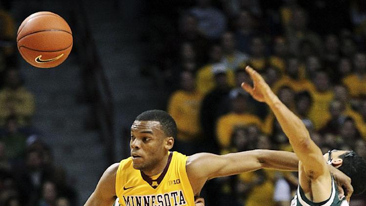 Michigan State guard Travis Trice, right, is fouled by Minnesota guard Andre Hollins (1) in the first half of their NCAA college basketball game, Monday, Dec. 31, 2012, in Minneapolis. (AP Photo/Andy Clayton King)