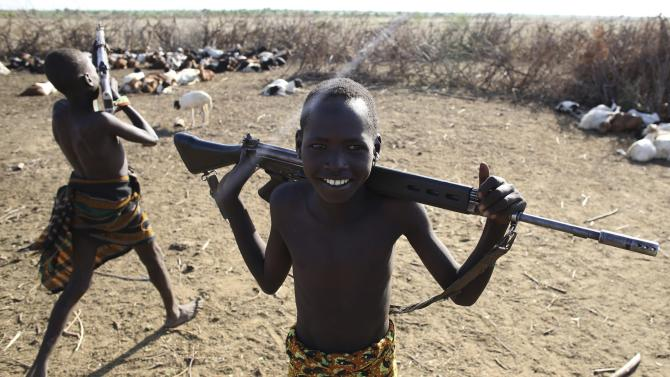 Turkana boys play with rifles in a village inside the Turkana region of the Ilemi Triangle