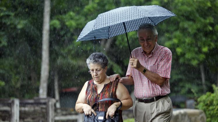 A couple uses an umbrella as it rains Ponce, Puerto Rico, Wednesday, July 31, 2013. Puerto Ricans are used to wet tropical weather, but the past few weeks have been the wettest ever recorded in the U.S. island territory. (AP Photo/Ricardo Arduengo)