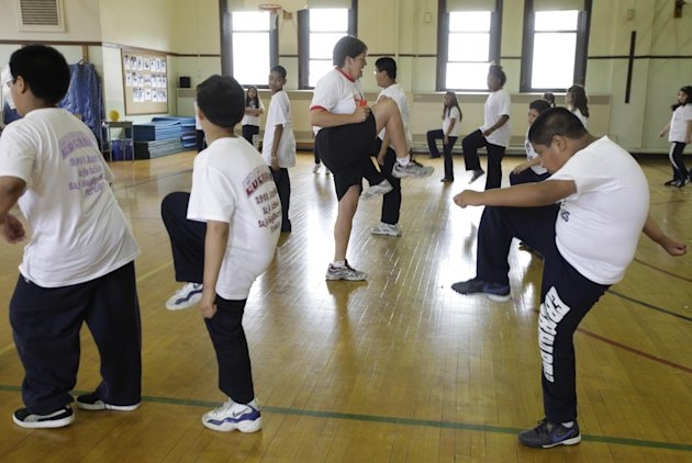 CORRECTS INFORMATION REGARDING THE STUDY'S RELEASE - FILE - In this May 26, 2009 file photo, Betty Hale, center, instructs a physical education class at Eberhart Elementary School in Chicago. Conventional wisdom says school gym classes make a big difference in kids' weight. But a report in the Thursday, Jan. 31, 2013 issue of the New England Journal of Medicine says this is one of many myths that are detracting from real solutions to the nation's weight problems. According to the report, gym classes often are not long, often or intense enough to make much difference. (AP Photo/M. Spencer Green, File)