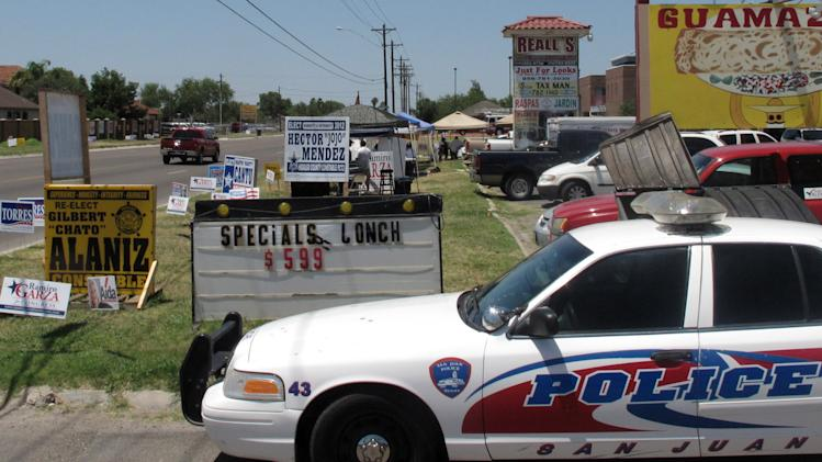 Police remain on a busy corner in San Juan, Texas, Tuesday, May 29, 2012 where one man holding a campaign sign was shot in the leg by someone in a passing vehicle. A polling station was nearby in a building that housed the police and fire departments. (AP Photo/Chris Sherman)