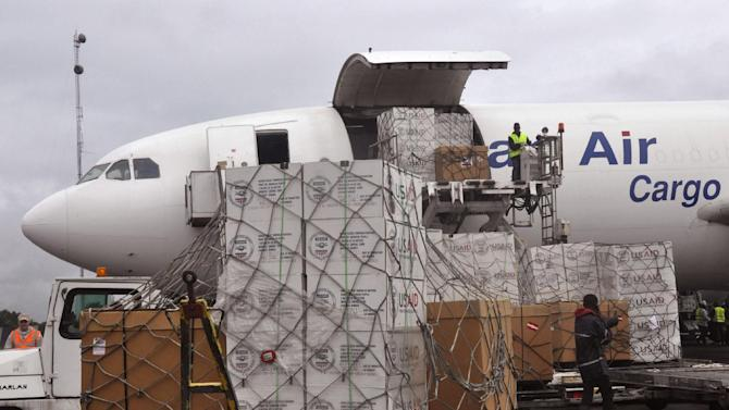 American Aid goods are offloaded from an airplane, to be used in the fight against the Ebola virus spreading in the city of Monrovia, Liberia, Sunday, Aug. 24, 2014. Two alarming new cases of Ebola have emerged in Nigeria, widening the circle of people sickened beyond the immediate group of caregivers who treated a dying airline passenger in one of Africa's largest cities. The outbreak also continues to spread elsewhere in West Africa, with 142 more cases recorded, bringing the new total to 2,615 with 1,427 deaths, the World Health Organization said Friday. (AP Photo/Abbas Dulleh)