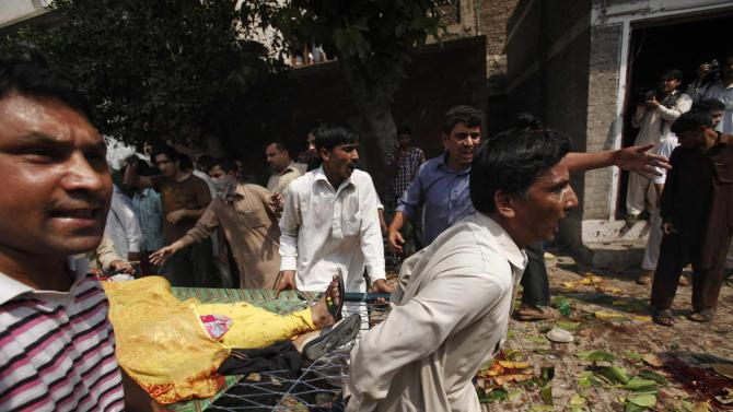 Men carry an injured women on a stretcher at the site of a suicide blast at a church in Peshawar