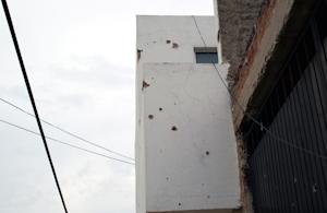 Bullet holes mark a house in Ocotlan, after the ambush …