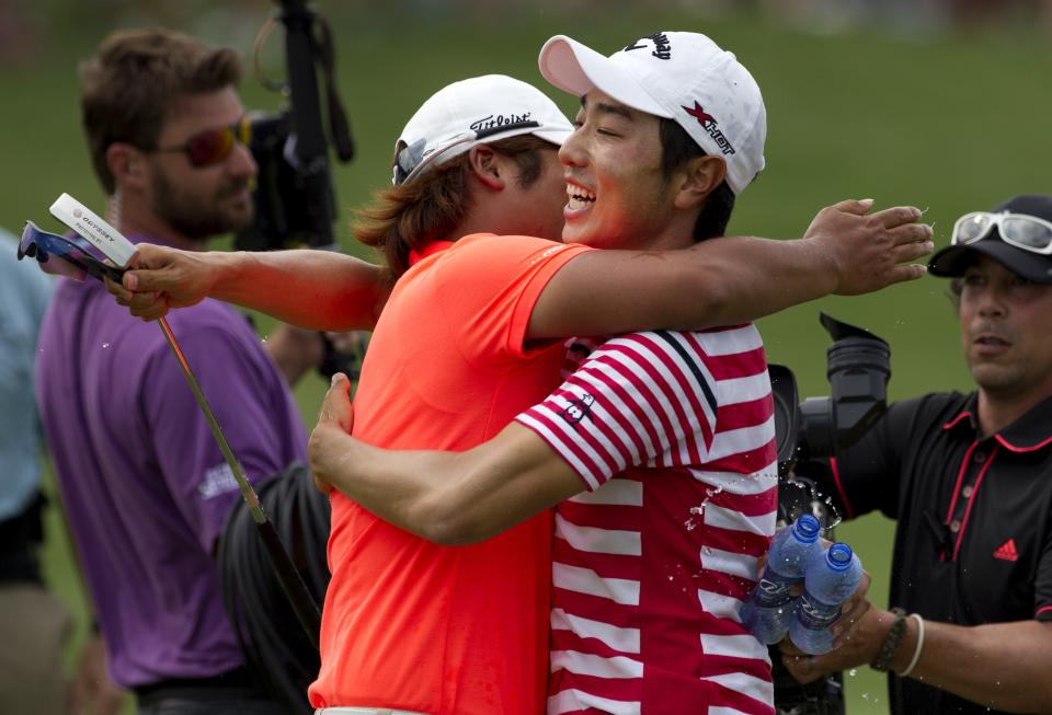 ADDS NAME OF GOLFER ON LEFT SEUNG-YUI NOH - Sang-Moon Bae of South Korea is congratulated by Seung-Yui Noh, also of South Korea, on the 18th green after Bae won the Byron Nelson golf tournament Sunday, May 19, 2013, in Irving, Texas. (AP Photo/Tony Gutierrez)
