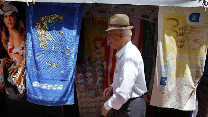 An elderly man walks past a kiosk selling towels printed with high-denomination euro banknotes and the map of Greece in central Athens, Wednesday, May 29, 2013. Greece's central bank says the economy is likely to contract by a further 4.6 percent in 2013 with unemployment set to reach 28 percent. The Bank of Greece's estimate, issued in a report published Wednesday, is worse than the 4.2 percent contraction predicted by the government and the country's rescue lenders. (AP Photo/Thanassis Stavrakis)
