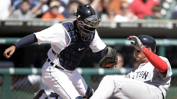 Boston Red Sox's Ryan Sweeney, right, scores past Detroit Tigers catcher Alex Avila on a sacrifice fly by Nick Punto in the third inning of a baseball game Sunday, April 8, 2012, in Detroit. (AP Photo/Duane Burleson)