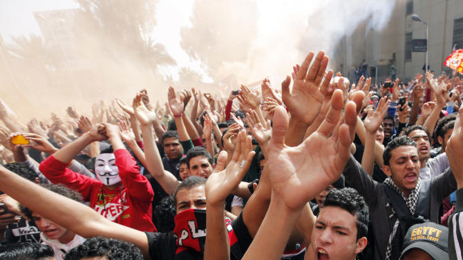 Egyptian soccer fans of the Al-Ahly club celebrate in front of their club in Cairo, Egypt, after an Egyptian court confirmed death sentences against 21 people for their role in a deadly 2012 soccer riot that killed more than 70 people in the city of Port Said, Saturday, March 9, 2013. (AP Photo/Amr Nabil)