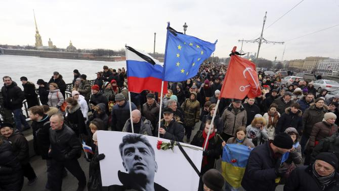 People march behind a banner to commemorate Kremlin critic Boris Nemtsov, who was shot dead on Friday night, in central St. Petersburg