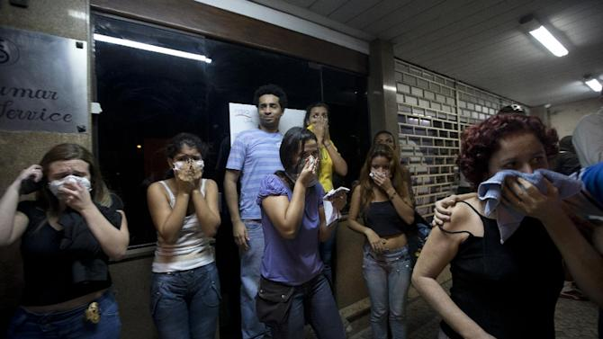FILE - This June 19, 2013 photo, residents cover their faces as protection from the tear gas shot by riot police at demonstrators during an anti-government protest in Rio de Janeiro's sister city, Niteroi, Brazil. Rio de Janeiro and Sao Paulo city leaders said that they reversed an increase in bus and subway fares that ignited anti-government protests. Many people doubted the move would quiet the demonstrations which have moved well beyond outrage over the fare hikes into communal cries against poor public services. (AP Photo/Silvia Izquierdo, File)