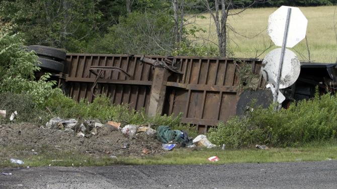 A tractor-trailer is seen lying on its side in the bushes on  Monday, July 11, 2011 in N. Berwick, Maine. An Amtrak train traveling at 70 mph smashed into a tractor-trailer in a fiery collision that killed the truck driver, injured a half-dozen others and sent flames more than three stories high, a witness and officials said. (AP Photo/Pat Wellenbach)