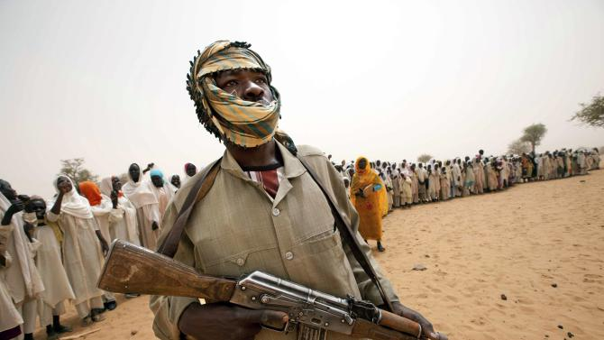 File picture of a member of SLA standing guard as people stand in line to welcome UNAMID delegation arriving to open a new clinic in Forog, north Darfur