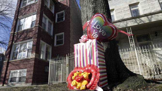 A makeshift memorial is seen in Chicago, Tuesday, March 12, 2013, at the site where 6-month-old girl Jonylah Watkins, and her father, a known gang member, were shot Monday, March 11. The girl, who was shot five times, died Tuesday morning. She became the latest homicide victim of a bloody gang war in Chicago when a man approached a van in which her father was changing her diaper and opened fire. Her father, Jonathan Watkins, was in serious but stable condition. (AP Photo/M. Spencer Green)