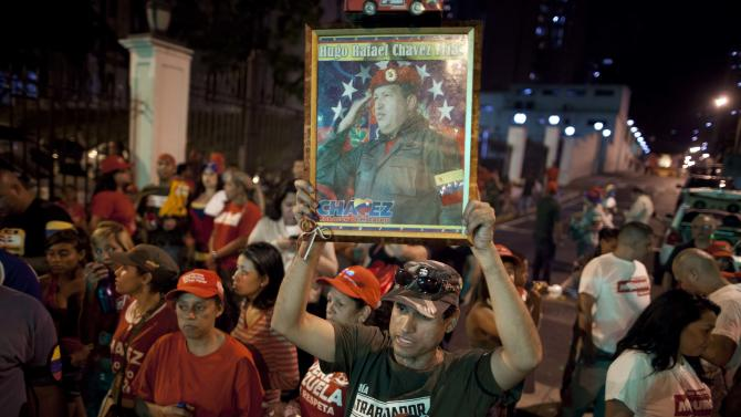 Chavista militants and government supporters, one holding a portrait of Venezuela's late President Hugo Chavez, wait for presidential election results outside the Miraflores Palace in Caracas, Venezuela, Sunday, April 14, 2013. Venezuelans went to the polls Sunday to choose the next president between Hugo Chavez's chosen successor, ruling party candidate Nicolas Maduro, and opposition candidate Henrique Capriles. (AP Photo/Ramon Espinosa)