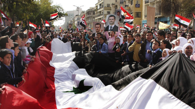 Pro-Syrian regime protesters, shout slogans and carry a giant Syrian flag during a demonstration against the Arab League decision to suspend Syria, in Damascus, Syria, on Sunday Nov. 13, 2011. Tens of thousands of pro-regime demonstrators gathered in a Damascus square Sunday to protest the Arab League's vote to suspend Syria over its bloody crackdown on the country's eight-month-old uprising. Saturday's Arab League decision was a sharp rebuke to a regime that prides itself as a bastion of Arab nationalism, but it was unlikely to immediately end a wave of violence that the U.N. estimates has killed more than 3,500 people since mid-March. (AP Photo/Bassem Tellawi)