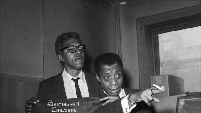 """FILE - In this Sept. 18, 1963 file photo, author James Baldwin, right, and Bayard Rustin, deputy director of the March on Washington, talk about civil rights incidents in Alabama during a news conference in New York. The two civil rights leaders called upon President John F. Kennedy to use troops to """"break the hold"""" of Gov. George Wallace, otherwise """"there will be rioting in Alabama"""" which will affect the entire nation. The arm band displayed was to be worn at a rally scheduled in New York on Sept. 22, 1963 """"to protest the brutal murder of Negro children in Birmingham."""" (AP Photo/File)"""