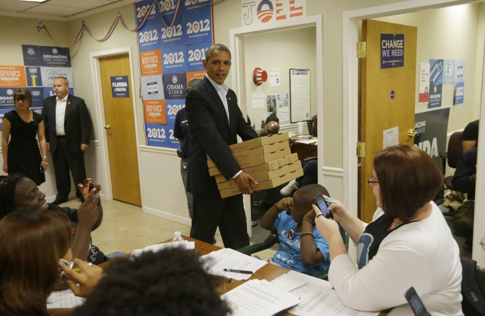 President Barack Obama walks in as he delivers pizzas to volunteers during an unscheduled visit to a local campaign field office, Sunday, Oct. 28, 2012 in Orlando Fla. (AP Photo/Pablo Martinez Monsivais)