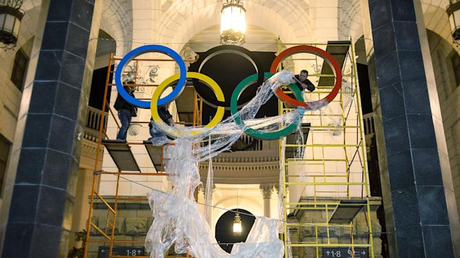 FILE - In this Monday, Oct. 28, 2013 file photo, workers are fixing the Olympic emblem at an entrance to the railway station of Russia's Black Sea resort of Sochi, Russia. Over the past few Olympics, NBC has shown more live coverage over the Internet than it has on TV. For the upcoming Winter Games, Comcast's Xfinity TV subscribers will be able to tap the breadth of that online coverage on their big screens. (AP Photo/Lesya Polyakova, File)