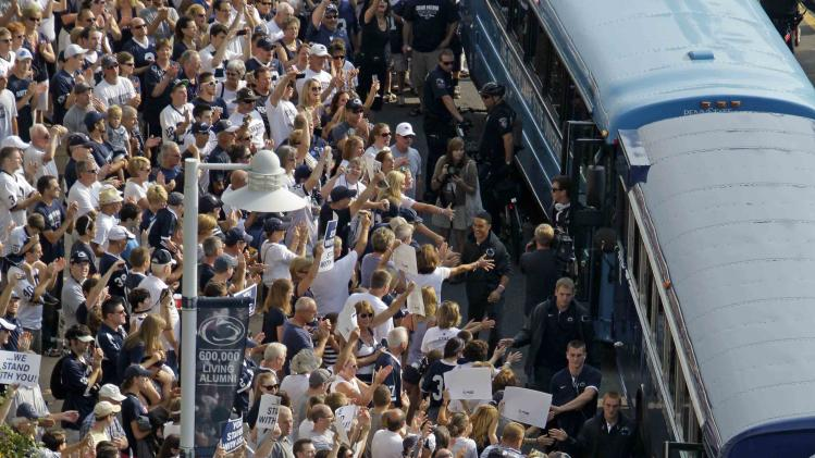 Penn State football fans cheer for the Penn State football team as they arrives by bus at Beaver Stadium for their season opener against Ohio in State College, Pa., Saturday, Sept. 1, 2012. (AP Photo/Gene J. Puskar)