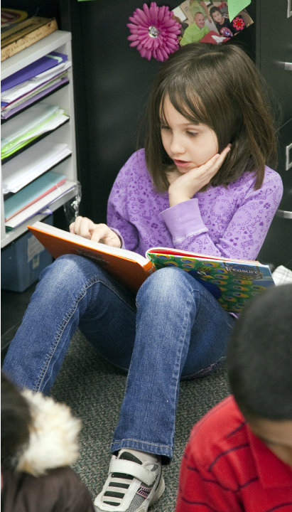 In this Jan. 23, 2013 photo Jefferson Elementary third grader Chloie DeLancy works on a reading assignment in Wichita, Kan.  Kansas is one of an increasing number of states that are not promoting stud