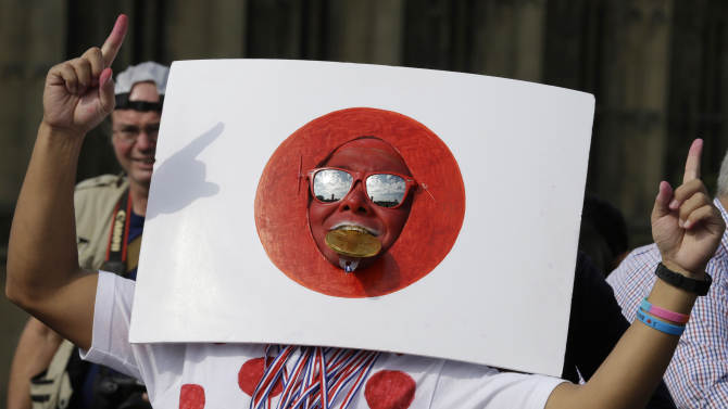 A Japanese supporter gestures next to the Houses of Parliament, prior to the start of the men's marathon at the 2012 Summer Olympics, at the 2012 Summer Olympics, London, Sunday, Aug. 12, 2012. (AP Photo/Luca Bruno)