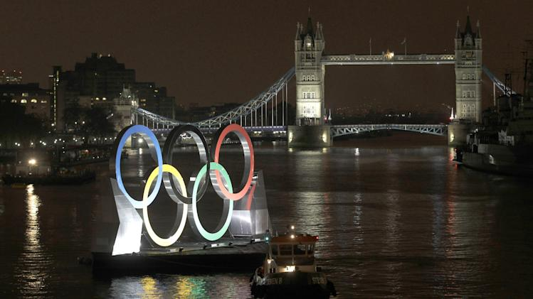 Backdropped by the historic Tower Bridge, a giant Olympic Rings floats on the River Thames in London in the run-up for the Olympic games, during its launch to mark 150-days until the start of the London 2012 Olympic games, Tuesday, Feb. 28, 2012.  (AP Photo/Sang Tan)