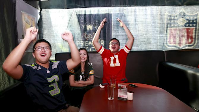 Filipino fans of NFL's Super Bowl 50 gesture as they watch a live telecast of the Denver Broncos playing against the Carolina Panthers at Skinny Mike's sports bar in Taguig city, metro Manila