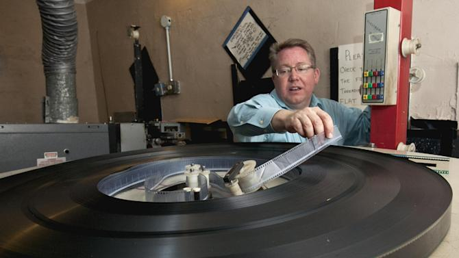 In this photo from Sept. 4, 2012, Thom Reeves, owner of the Isis movie theatre, treads a roll of 35 mm film in the projection room in Crete, Neb. . The Isis Theatre hasn't changed much since it opened 86 years ago, but as the movie industry phases out the traditional 35 mm film reels in favor of digital media, the Isis' owner must come up with $85,000 to buy new projection equipment, computers, a sound system and even a different screen. It is a huge financial burden for the small theatre. (AP Photo/Nati Harnik)