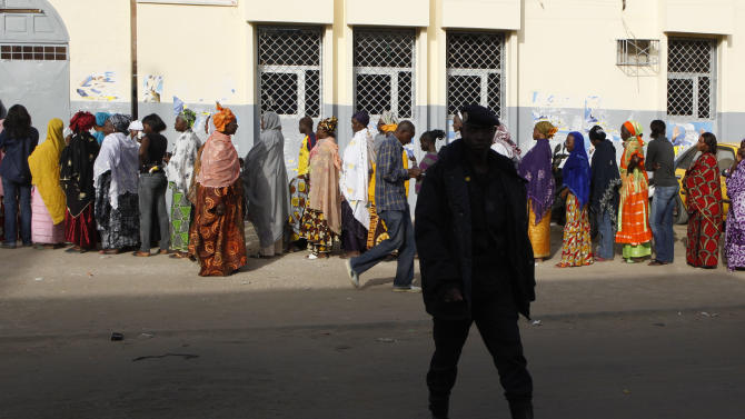 A paramilitary policeman providing poll security walks past a line of women waiting to vote, outside a polling station in the Parcelles Assainies neighborhood of Dakar, Senegal Sunday, Feb. 26, 2012. After weeks of riots, Senegalese voters began casting their ballots Sunday in an election that threatens the country's image as one of the oldest and most robust democracies in Africa. This normally unflappable nation on the continent's western coast has been rocked by back-to-back protests following the decision of its 85-year-old leader Abdoulaye Wade to seek a third term. (AP Photo/Rebecca Blackwell)