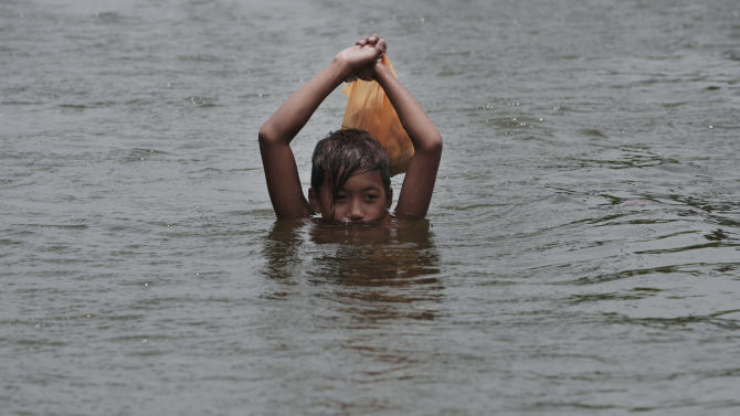 A Filipino boy raises a bag of bread to keep it dry as he negotiates deep floods at Malabon city, north of Manila, Philippines, Wednesday Aug. 1, 2012. Fierce winds and heavy rains from the slow-moving Typhoon Saola battered the country, displacing 154,000 people. (AP Photo/Aaron Favila)