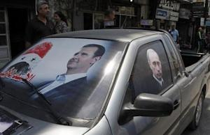 Election poster of Syria's President Bashar al-Assad and a photo of Russian President Vladimir Putin are seen on a car at al-Qardahah town
