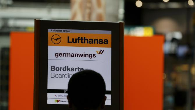 A passenger stands in front of a German airlines Lufthansa and Germanwings sign at Duesseldorf airport