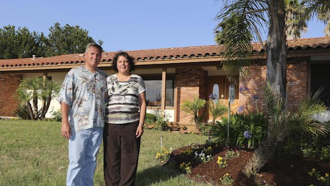 In this Wednesday, July 3, 2013, photo, Robert and Emerald Oravec pose outside their new home in Vista, Calif., Wednesday, July 3, 2013. The couple sold a 900 square foot condominium for $80,000 more than they thought possible and brought a 2200 square foot home. (AP Photo/Lenny Ignelzi)