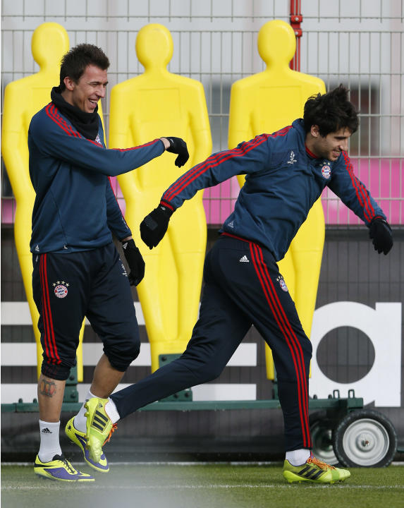 Bayern's Mario Mandzukic of Croatia, left, jokes to team mate Javier Martinez of Spain as he arrives for a last training session prior the Champions League group D soccer match between FC Bayern M