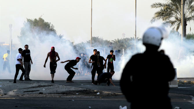 Bahraini anti-government protesters clash with riot police in Sadad, Bahrain, on Saturday, Sept. 29, 2012, after the politically charged funeral for Ali Hussein Niema, 17, who allegedly was shot dead by riot police late Friday. The death could bring fresh protests by Shiite-led groups seeking a greater political voice in the Sunni-ruled Gulf kingdom. (AP Photo/Hasan Jamali)