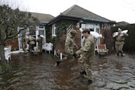 British army soldiers place sandbags at the entrance to a flooded house at Chertsey, England, Wednesday, Feb. 12, 2014. The River Thames has burst its banks after reaching its highest level for many years, flooding riverside towns upstream of London, including Chertsey which is about 30 miles west of central London. Some hundreds of troops have been deployed to assist with flood protection and to get medical assistance to the sick and vulnerable.(AP Photo/Sang Tan)