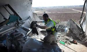 An Israeli Zaka emergency services volunteer works in an apartment that was hit by a rocket fired by Palestinian militants, killing three people on Nov. 15 in Kiryat Malachi, Israel.