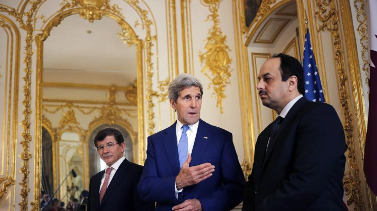 U.S. Secretary of State John Kerry stands with Qatari Foreign Minister Khaled al-Attiyah and Turkish Foreign Minister Ahmet Davutoglu in Paris
