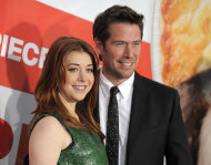 FILE - This March 19, 2012 file photo shows actress Alyson Hannigan, a cast member in &quot;American Reunion,&quot; posing with her husband, actor Alexis Denisof, at the premiere of the film in Los Angeles. Hannigan obtained a temporary restraining order on Wednesday, Feb. 13, 2013 claiming a New Hampshire man recently released from a mental institution has been threatening to kill her and harm her family in online postings. (AP Photo/Chris Pizzello, file)