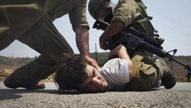 Israeli security forces detain an unidentified protester during a joint pro-Palestinian demonstration held by foreign, Israeli and Palestinian demonstrators in the West Bank village of Nabi Saleh, Saturday, July 9, 2011. Some of the international pro-Palestinian activists questioned at Israel's airport over the weekend have reached the West Bank and participated in anti-Israel protests Saturday. (AP Photo/Oren Ziv)
