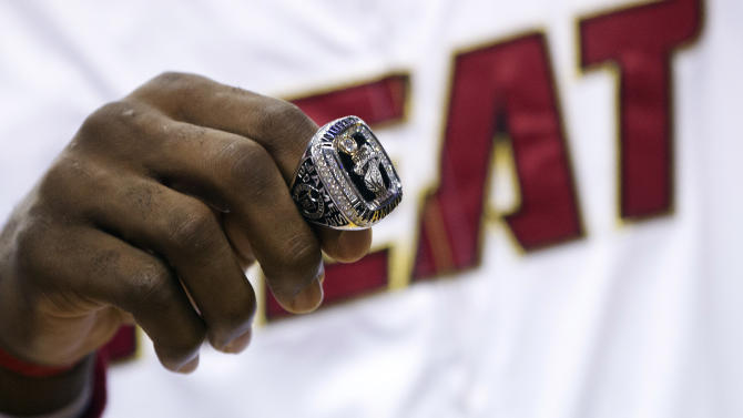 Miami Heat's LeBron James holds his 2012 NBA Finals championship ring during a ceremony before a basketball game against the Boston Celtics, Tuesday, Oct. 30, 2012, in Miami. (AP Photo/J Pat Carter)