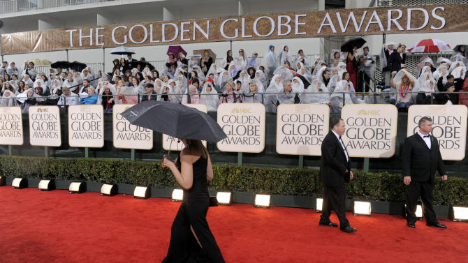 FILE- In this Sunday, Jan. 17, 2010, file photo, a publicist walks down the red carpet as it rains before the 67th Annual Golden Globe Awards in Beverly Hills, Calif.  A federal judge ruled on April 30, 2012, that a $150 million agreement keeping the Globes on NBC is valid, siding with the show's longtime producers and against the organization that organizes the glitzy awards gala each year. (AP Photo/Chris Pizzello, File)